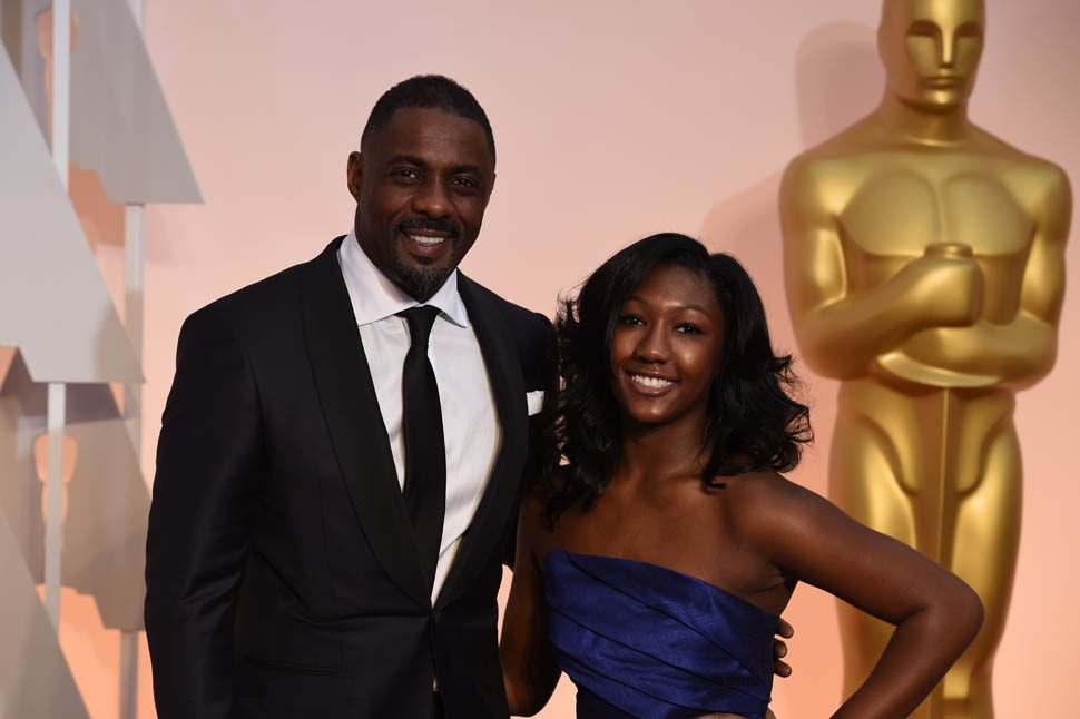 Actor Idris Elba (L) and Isan Elba pose on the red carpet for the 87th Oscars on February 22, 2015 in Hollywood, California. AFP PHOTO/ MARK RALSTON (Photo credit should read MARK RALSTON/AFP/Getty Images)